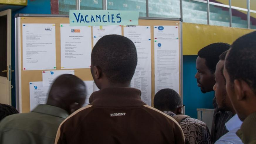 Job seekers look for job opportunities on a notice board displayed at the third Kigali Employment Fair at Petit Stade in Remera earlier this week. (Timothy Kisambira)