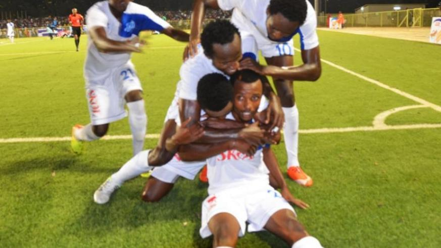 Rayon Sports' Savio Nshuti (foreground) is mobbed by his teammates after scoring the third goal in the 3-1 win over Police on Saturday.  (S. Ngendahimana)