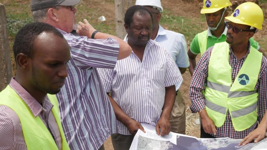Dr Canisius Kanangire (R) Lake Victoria Basin Commission Executive Secretary and water and sanitation experts from across EAC inspect Water Plant Designs in Nyanza District, Southe....