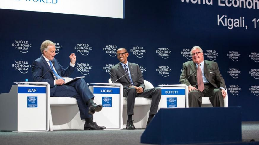 President Kagame and US philanthropist Howard Buffett (R) follow through submission of former British Prime Minister Tony Blair during a panel discussion at WEF meeting in Kigali y....