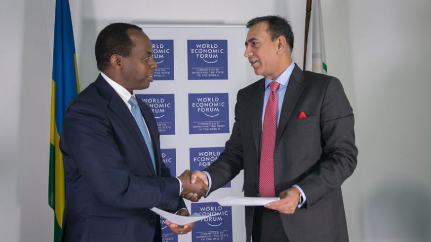 Gatare and Malhotra exchange documents after the signing in Kigali yesterday. (Courtesy)