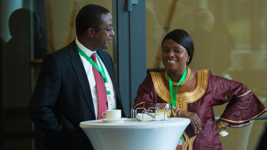 The Minister for Natural Resources, Dr Vincent Biruta (L) chats with Christine Sagno, Guinean minister for environment, water and forests during a breakfast meeting for environment....
