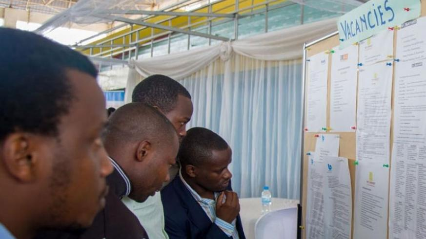 Jobseekers look for job opportunities on a notice board displayed at the third Kigali Employment Fair at Petit Stade in Remera, Kigali earlier this year. (File.)