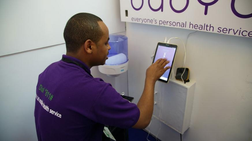 A Babyl staffer explains how to use purple machine, at a booth yesterday in Kigali. (Teddy Kamanzi.)