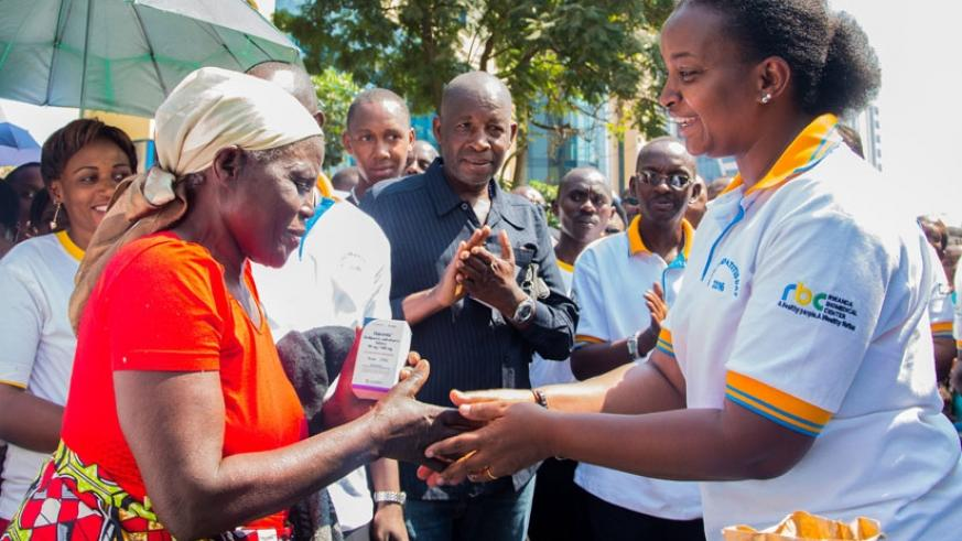 RBC director general Dr Jeanine Condo shakes hands after giving free medicine to a Hepatitis patient during the event to mark World Hepatitis Day at Kigali Car-Free Zone on Thursda....