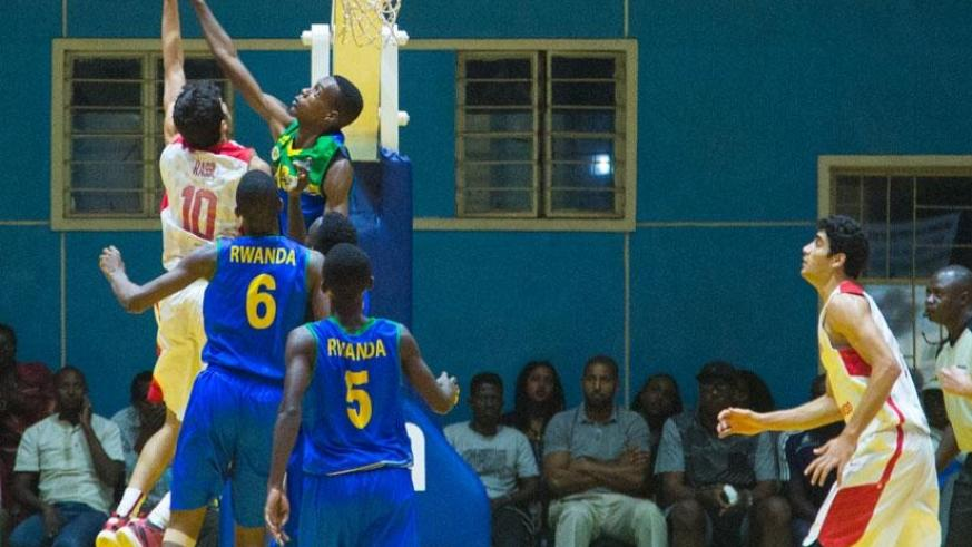 Osborn Shema of Rwanda blocks Mohamed Rassil Adam of Tunisia during the fourth quarter of their quarter-final game of the 2016 FIBA-Africa U18 Championship at Amahoro indoor stadiu....