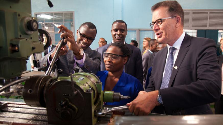 Marie Mukahirwa, a student of IPRC-Kigali (L), demonstrates how a machine operates to Education minister Papias Musafiri (L), IPRC-Kigali principal Diogene Mulindahabi (C) and Germ....