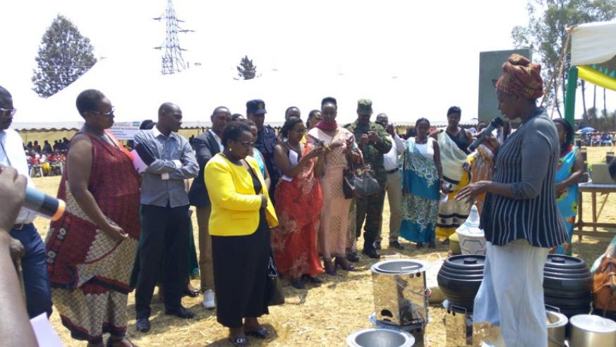 An unidentified woman explains about her environmentally-friendly stoves to local leaders. She was among other women who are helping the communities. / Julius Bizimungu.