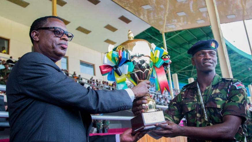 Defence minister James Kabarebe hands over the football trophy to a representative of Kenya Defence Forces team during the closing ceremony of the 10th EAC Military Games at Amahor....