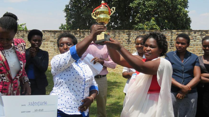 Mayor Uwamariya (L) hands over a trophy to the best performing cooperative, Tuzamurane, during the closing ceremony of the 10-day training in Muhanga District on Thursday. / John Mbaraga.