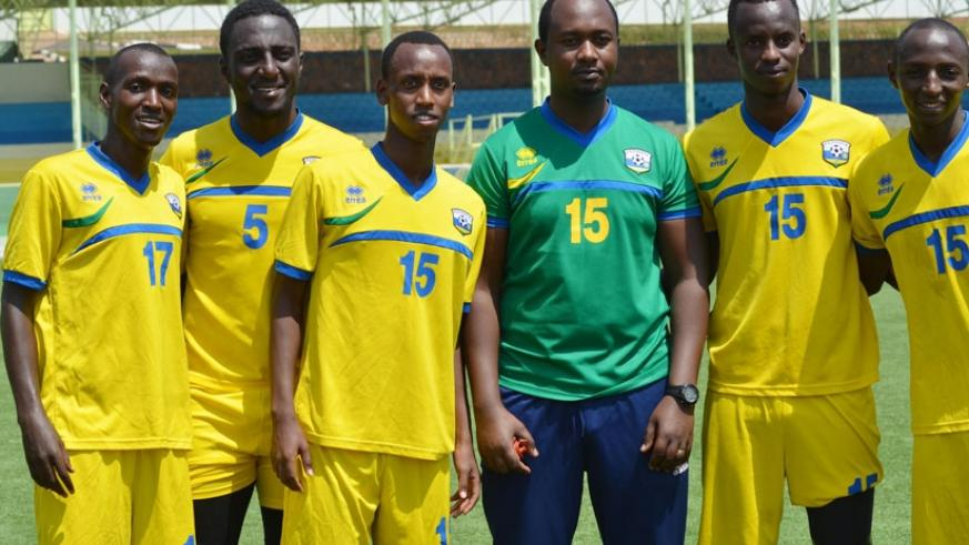 Newly appointed Amavubi interim assistant coach Mashami and some players take a break from training to pose for the cameras at Kigali Regional Stadium last week. / Sam Ngendahimana.