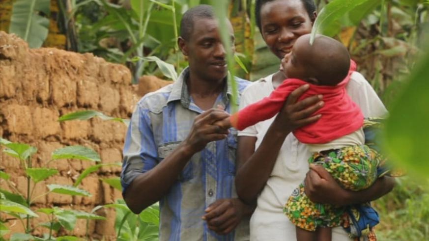 Theophile and Marceline carrying their son who is handicapped.