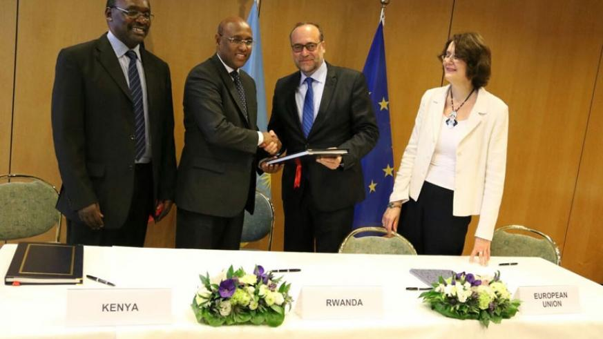 Mohamed (2nd L) and Slovakiam envoy to EU Peter Javorcik (2ndR) exchange the signed agreement as Kanimba (L) and  Sandra Galina, of the European Commission, look on.  (Courtesy)