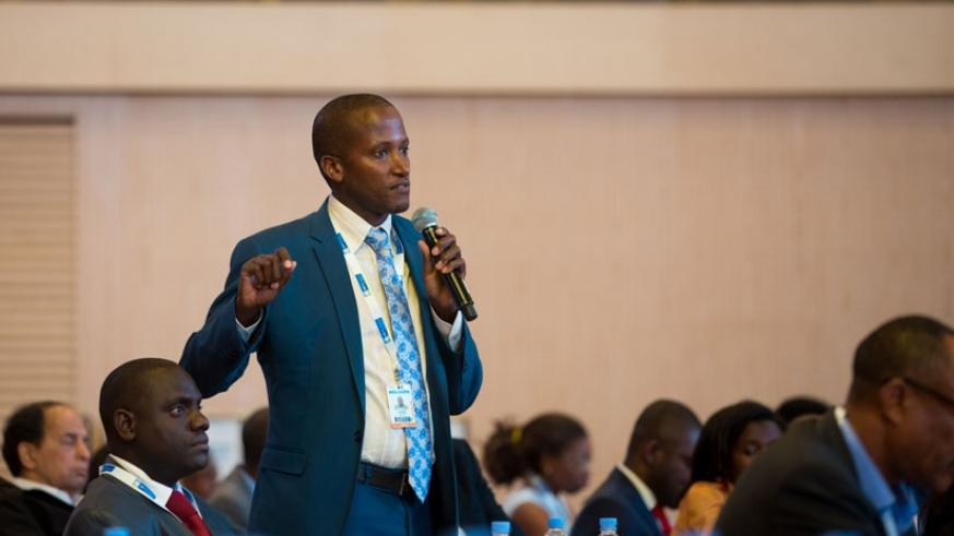 A participant asks a question during a panel discussion. / Timothy Kisambira.