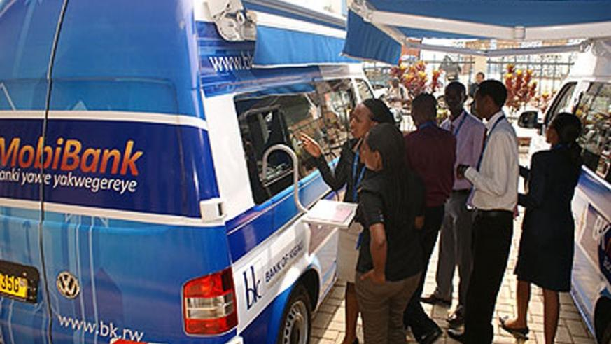 New clients consult bank officials at Bank of Kigali mobile banking van recently. (File)