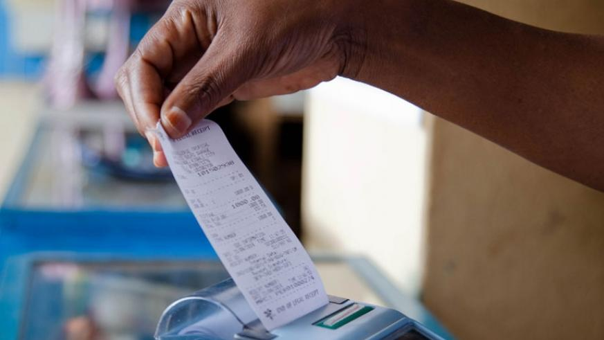 A trader pulls a receipt out of a billing machine at Mateus in Kigali. (File)