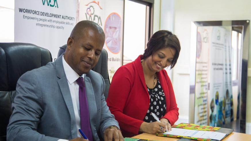 Jerome Gasana, the director general of WDA, and Dr Priya Ramluggun-Essoo, head of Business Development of Rushmore, sign the MoU on Wednesday in Kigali. (Faustin Niyigena)