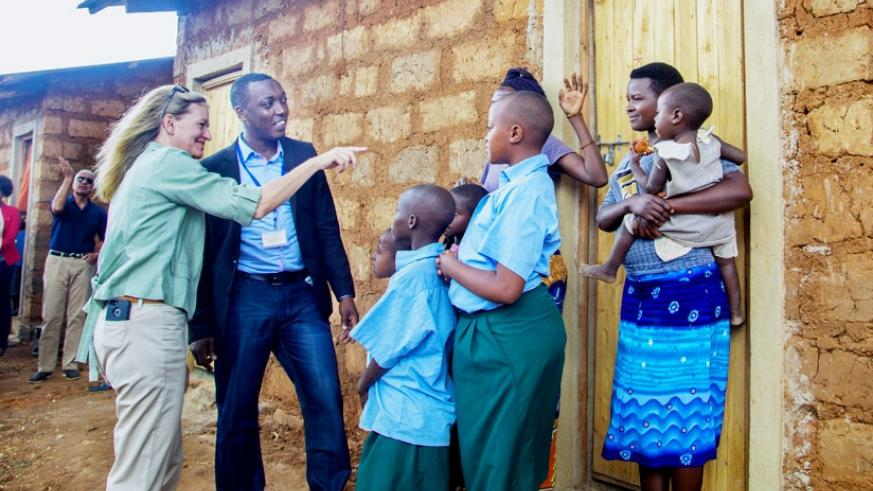 Amb. Barks-Ruggle with Aristarique Ngoga, the Mahama camp manager, in a light moment with a family that was given a semi-permanent house.  / Faustin Niyigena