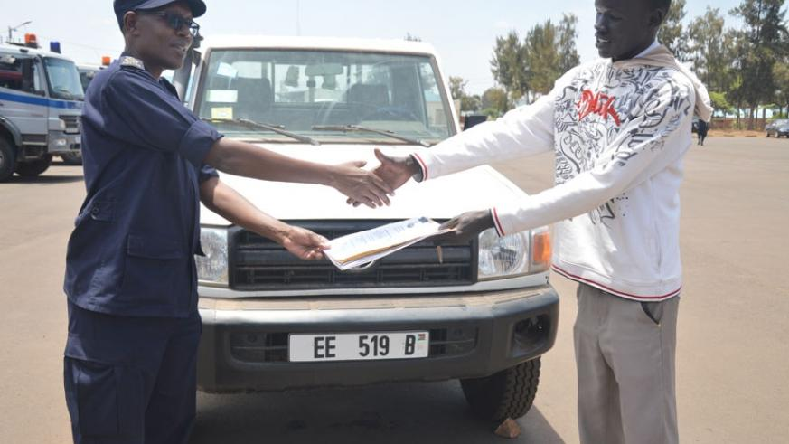 Tony Kulamba, the Commissioner for Interpol and Cooperation at Rwanda National Police, hands over the recovered vehicle to Jacob Garang Deng, a South Sudanese national, at the Forc....