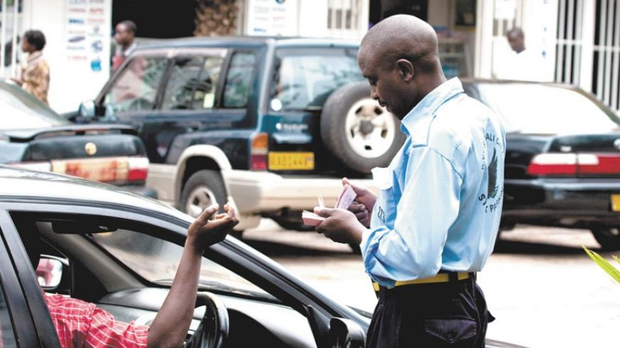 A parking attendant issues a ticket to a motorist in Kigali. Motorists have called for a review of the street parking system. / File.