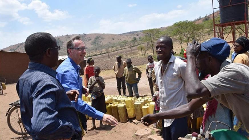 Water for Growth Team Leader, Ebel Smidt and the Head of the Integrated Water Resource Management Department, Vincent de Paul Kabalisa discuss with residents who came to fetch at t....