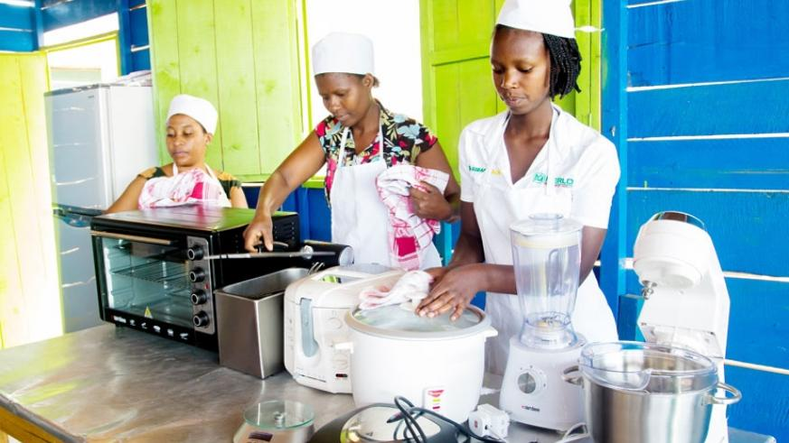 Trainees prepare cooking equipment for a lesson. (Photos by Faustin Niyigena)