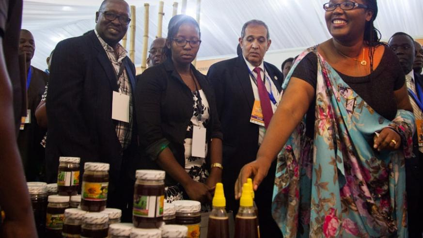 Dr Mukeshimana (R) visits one of the stands during the beekeeping exhibition. (Nadege Imbabazi)