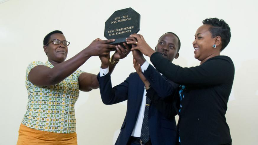 Kamonyi vice mayor in charge of social affairs Prisca Uwamahoro (L) and  the National Youth Council coordinator for Kamonyi, Ernest Kamanzi, (C) receive the district's award for to....