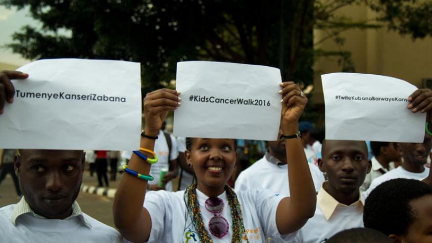 Youths raise placards during the kids cancer walk awareness campaign at car-free zone in Kigali. / Timothy Kisambira