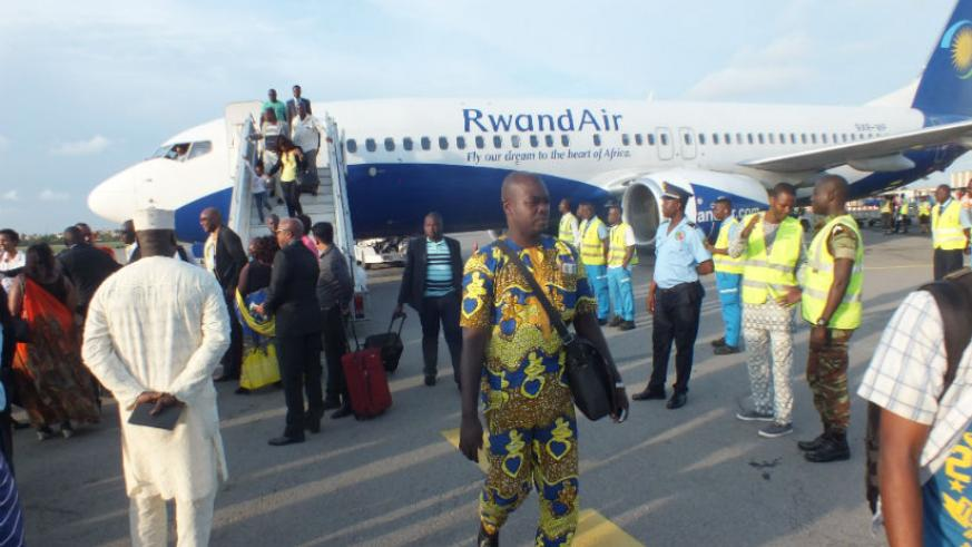 Passengers disembark from a RwandAir flight upon landing in Cotonou, the capital of Benin, officially marking the launch of the national flag carrier's flights to the West African ....