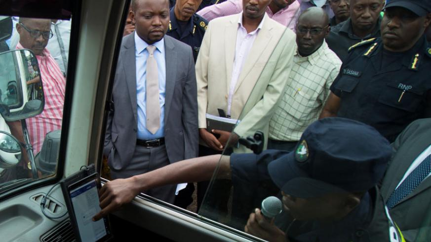 A traffic officer shows government officials how speed governors will work in public vehicles. (Timothy Kisambira)