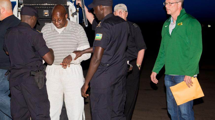 Genocide suspect Dr Leopold Munyakazi gets handcuffed after landing at Kigali International Airport yesterday. / Photographs: by Faustin Niyigena