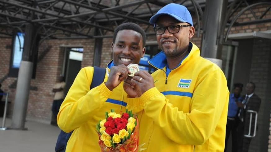 FERWACY president Bayingana (R) with Hadi show off the gold medal the Rwandan rider won at the 2015 All-Africa Games Road Race. (File photo)
