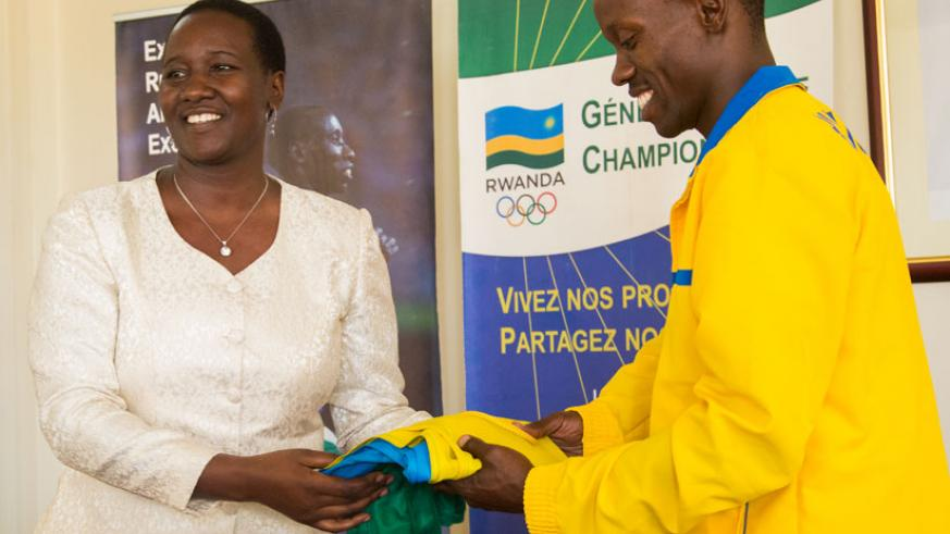 Muvunyi receives the national flag from Sports and Culture minister Julienne Uwacu ahead of the Paralympics team departure for Rio. / Faustin Niyigena.