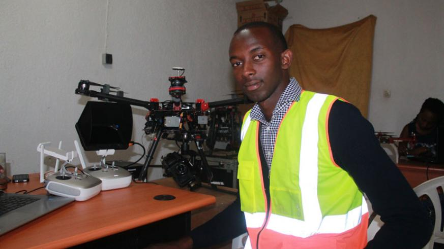 Teddy Segore poses by one of the drones he pilots. / Moses Opobo