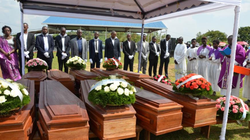 Bosco Ntagungira (4thR), a priest, leads prayers attended by Gasabo local government officials at the burial. / Elias Hakizimana.