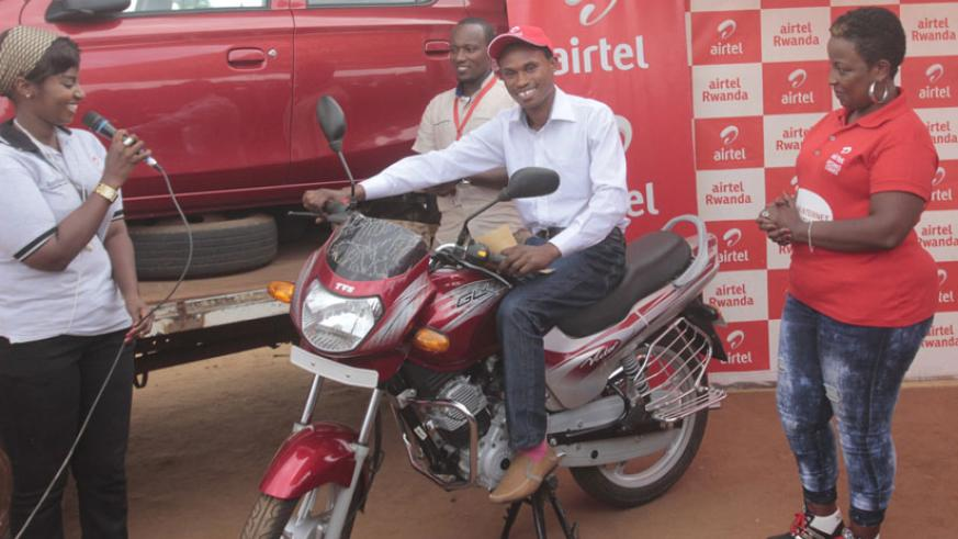 Mbarushimana tries out the motorcycle as Airtel officials cheer. / Francis Byaruhanga.