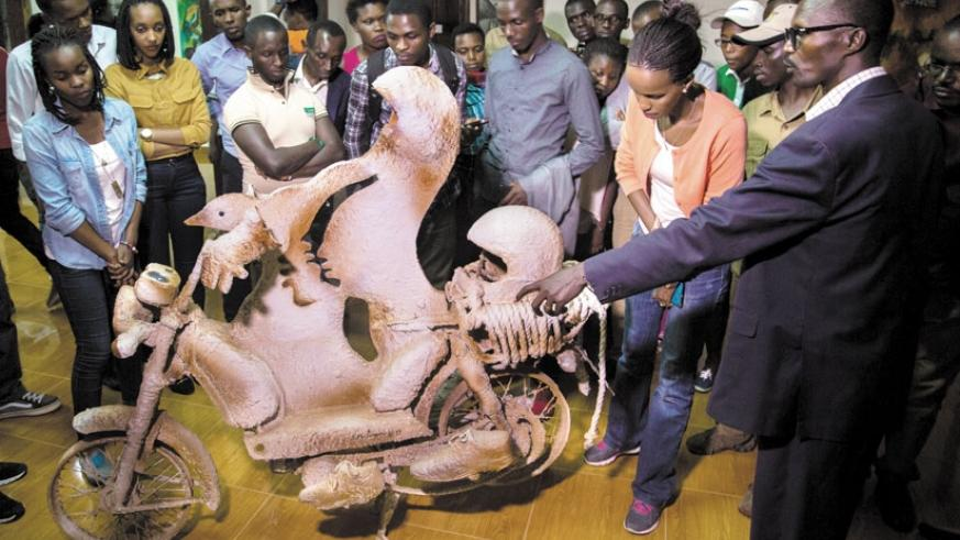 A guide explains to local tourists about his artwork at the Nyanza museum last week. (File)