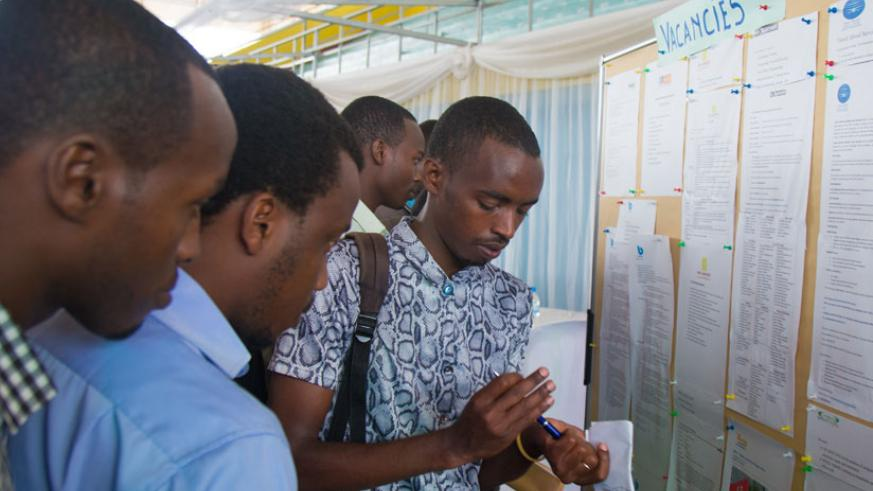 Job seekers look for job opportunities on a notice at Kigali Employment Fair at Petit Stade in Remera earlier this year. / File.