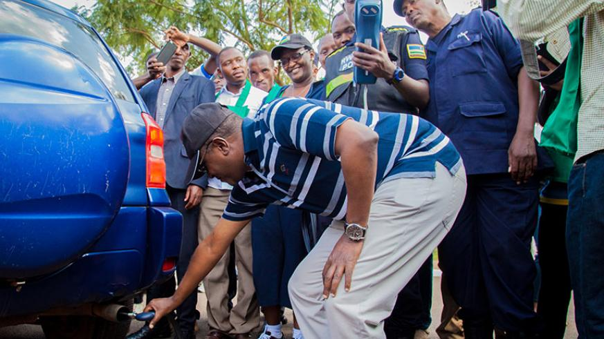 The Minister for Natural Resources, Dr Vincent Biruta, tests levels of carbon emissions from a car as police officers verify if the results match with the environmental standards. / File.