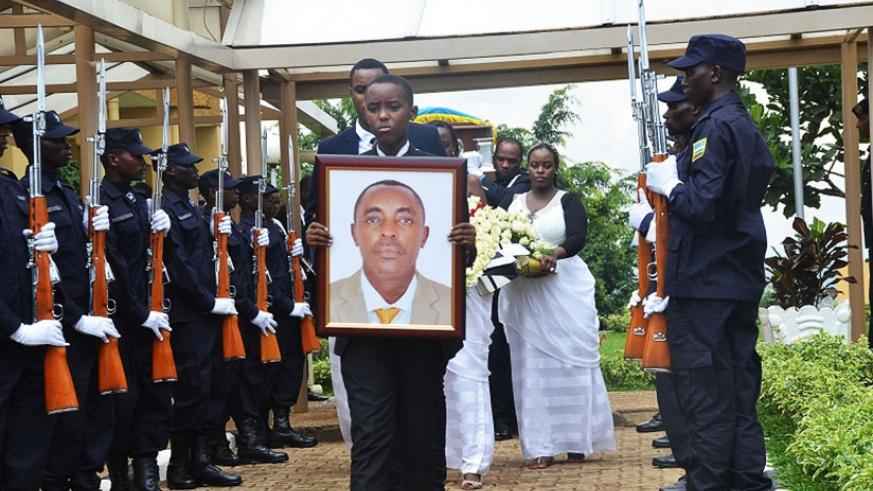 One of Mucyo's children holds a portrait of his father as the body arrived at parliament yesterday where the deceased was commended for exceptional service. / Sam Ngendahimana.