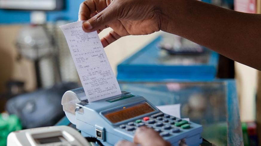 A trader pulls a receipt out of an electronic billing machine (EBM) in Kigali. A new law that seeks to make the use of EBMs mandatory for every business in the country to end unfai....
