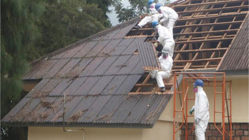 Technicians remove asbestos roofing material off a building at Gishari PTC. / File