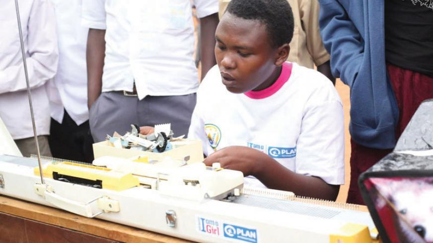 A girl uses a knitting machine donated to her by Plan International Rwanda during the International Girl Child Day celebrations in Gatsibo District on Tuesday. / Kelly Rwamapera.