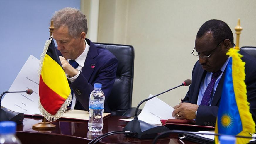 Gatete (R) and Amb. Pauwels sign the financial agreement in Kigali, yesterday. N. Imbabazi. File.