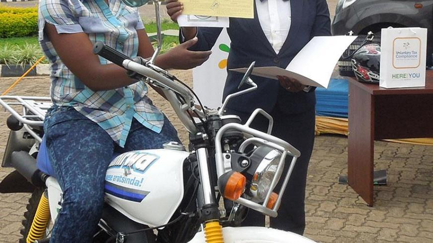Niyigena receives the motorcycle documents from Drocella Mukashyaka, the RRA deputy commissioner for taxpayer services. / Appolonia Uwanziga