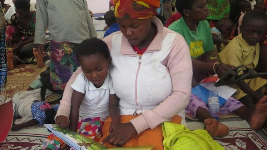 A parent helps her child to practice how to read. / Francis Byaruhanga