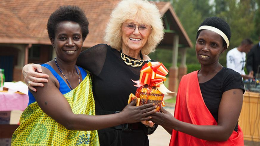 The Executive Director of International Organisation for Women and Development, Barbara Margolies (C), receives a gift from women who recovered from fistula after surgery. The team....