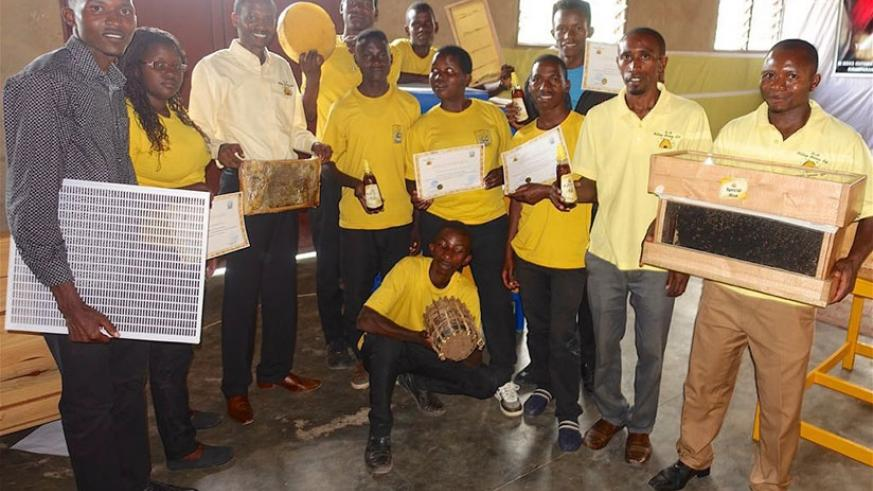 K+H staff pose for a group photo with students carrying beehives. / Sharon Kantengwa.