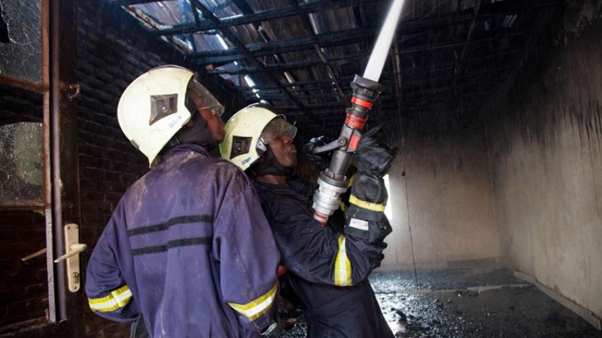Fire fighters put out a fire in Nyabugogo last year. Most public buildings in Kigali still lack fire-fighting equipment as per a 2015 Ministerial Order. (File photo)